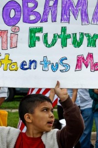 A young protester holds up a sign urging Obama to change the dreamers' future. Photo by Sasha Yimel/Flickr.