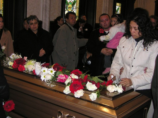 Gilberto Soto's sister Maria placing flowers on his casket